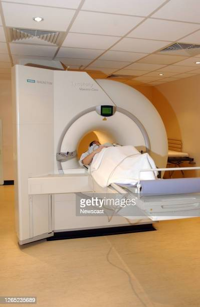 A female patient lies on the examination table of a magnetic resonance imaging scanner which is primarily used to visualize body structure and...