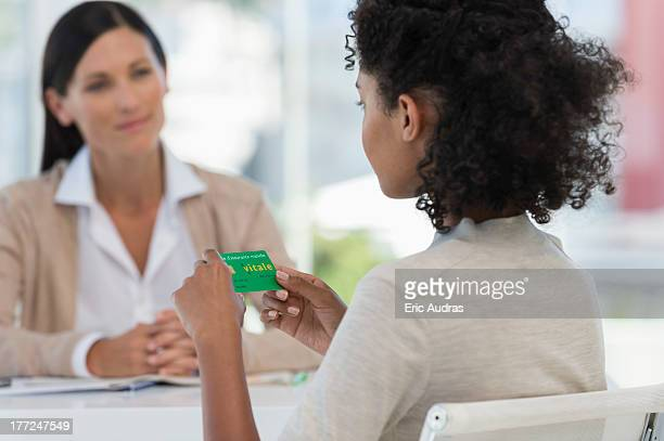 Female patient looking at a health insurance card