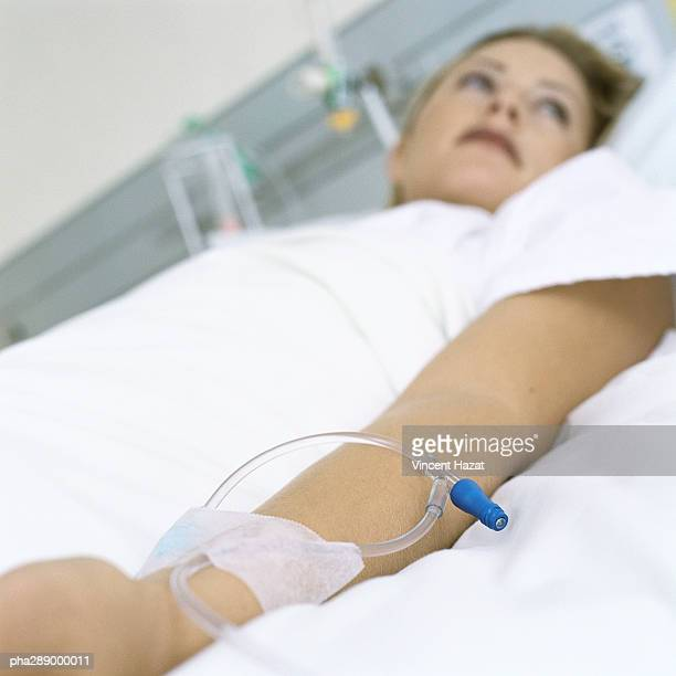 female patient lying in hospital bed - iv going into an arm stock photos and pictures