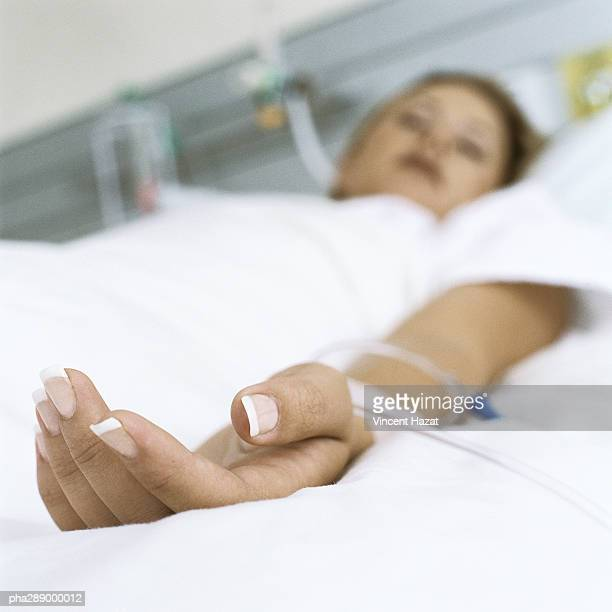 female patient lying in hospital bed - iv drip womans hand stock pictures, royalty-free photos & images
