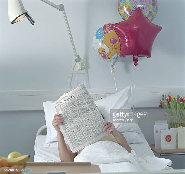 Female patient reading newspaper in hospital bed