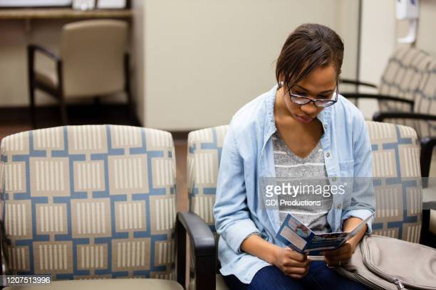 female patient reads brochure in er waiting room - pamphlet stock pictures, royalty-free photos & images
