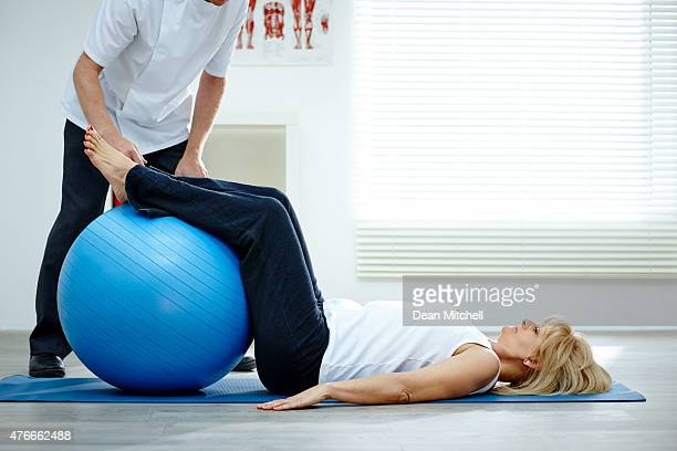 female patient working with physical therapists pilates exercise - fitness ball stock pictures, royalty-free photos & images