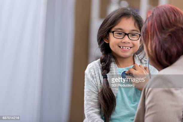 female pediatrician listens to young patient's heartbeat - emergency medicine stock pictures, royalty-free photos & images