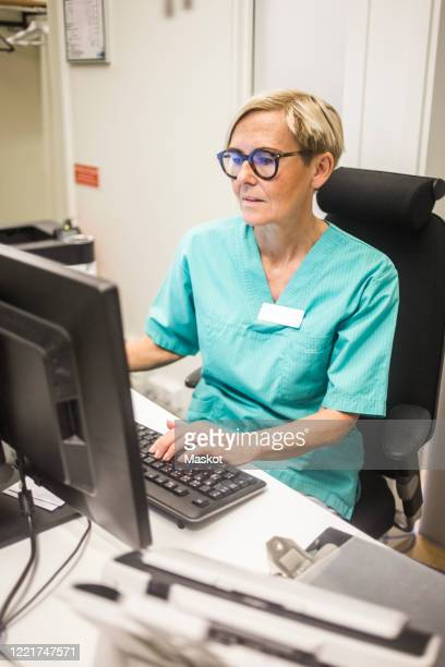 female pediatrician working on computer while sitting in hospital - medical receptionist uniforms stock pictures, royalty-free photos & images