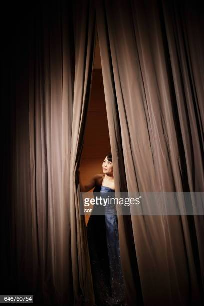 Female peeking through curtains of concert hall stage