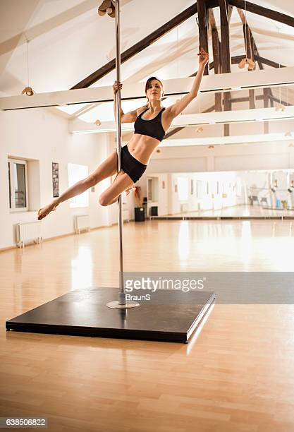 Female performer exercising pole dancing in a studio.