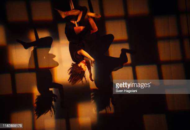 female performer hanging from rope on stage - burlesque stock pictures, royalty-free photos & images