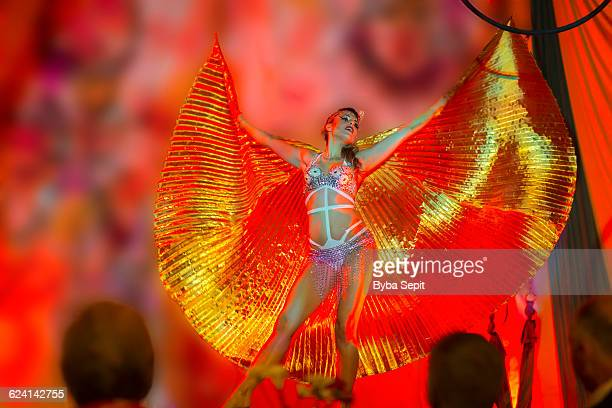 Female performer on a stage wearing golden wings.