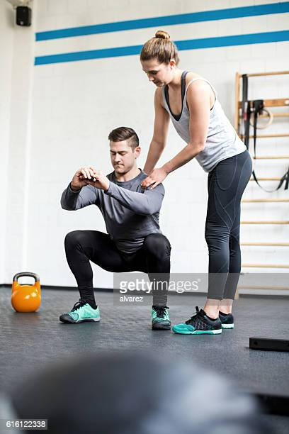 Female personal trainer guiding man at gym