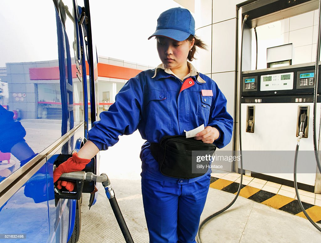 female petro station attendant filling gas into a vehicle
