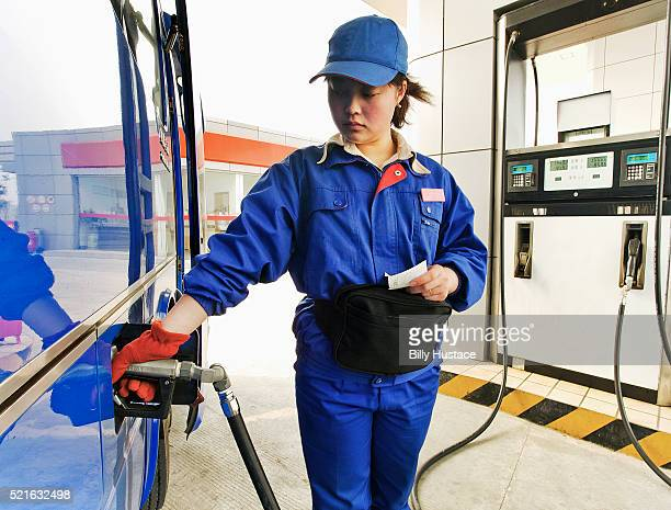 Female petro station attendant filling gas into a vehicle.