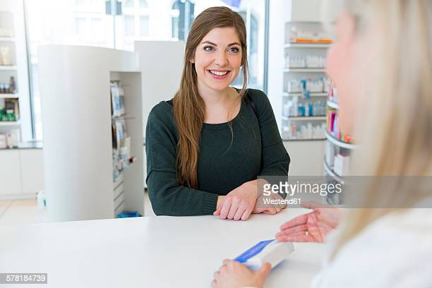 Female pharmacist advising female customer