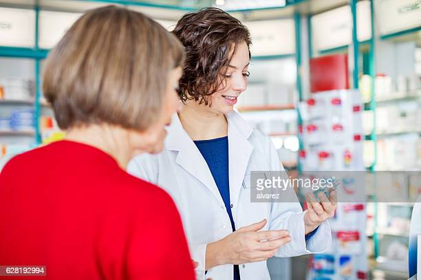 Female pharmacist assisting senior customer