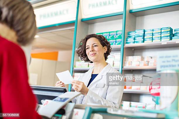 Female pharmacist assisting to customer in pharmacy