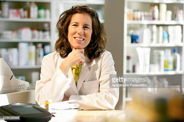 female pharmacist at counter of retail pharmacy - blacksburg stock pictures, royalty-free photos & images