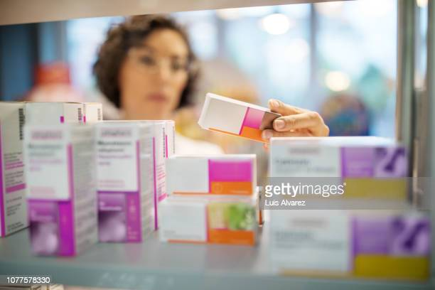 female pharmacist checking medicines on rack - medicijnen stockfoto's en -beelden