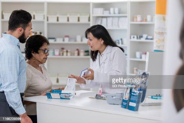 female pharmacist explains dosage instructions to customer - generic drug stock pictures, royalty-free photos & images