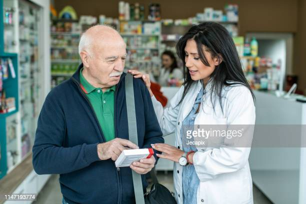 female pharmacist giving medications to senior customer - pharmacist stock pictures, royalty-free photos & images