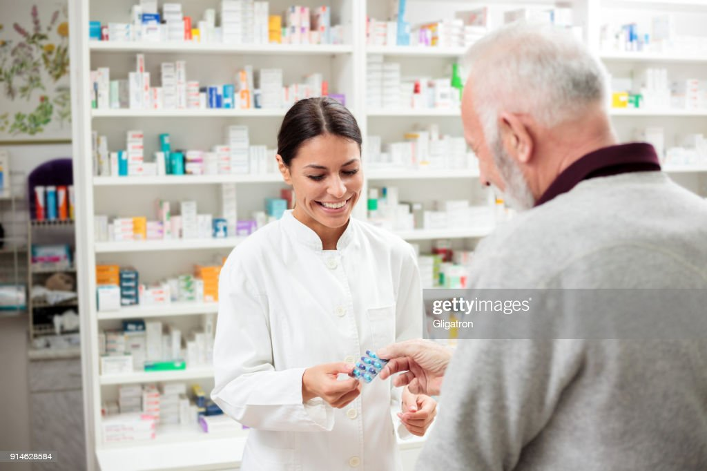 Female pharmacist giving medications to senior customer : Stock Photo