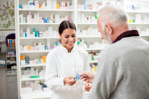 Female pharmacist giving medications to senior customer 914628584