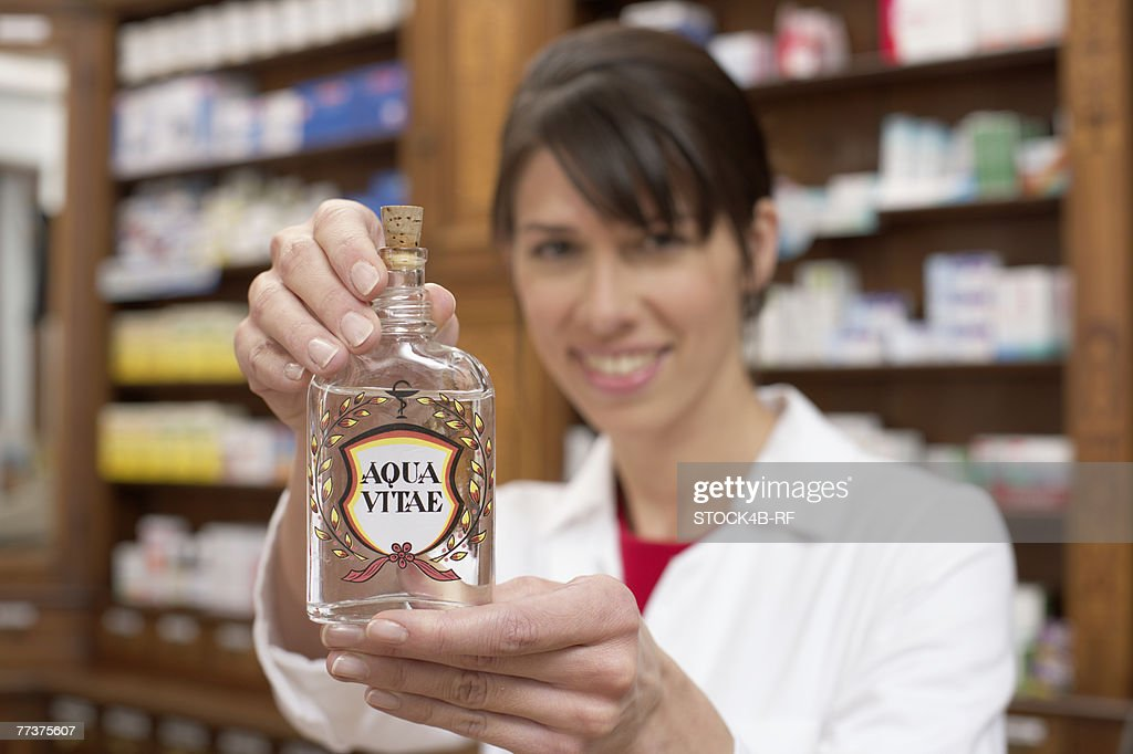 Female pharmacist holding a bottle of Aqua Vitae (aquavit, water of life) at camera : Photo