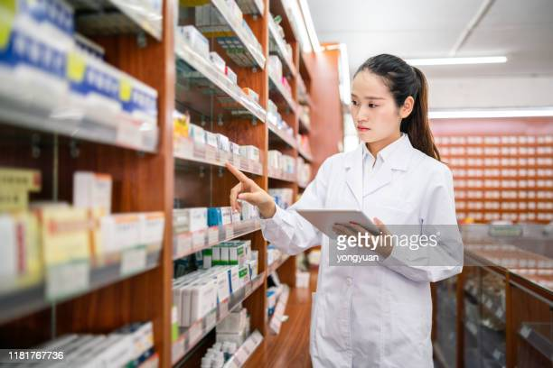 female pharmacist managing shelves - arranging stock pictures, royalty-free photos & images
