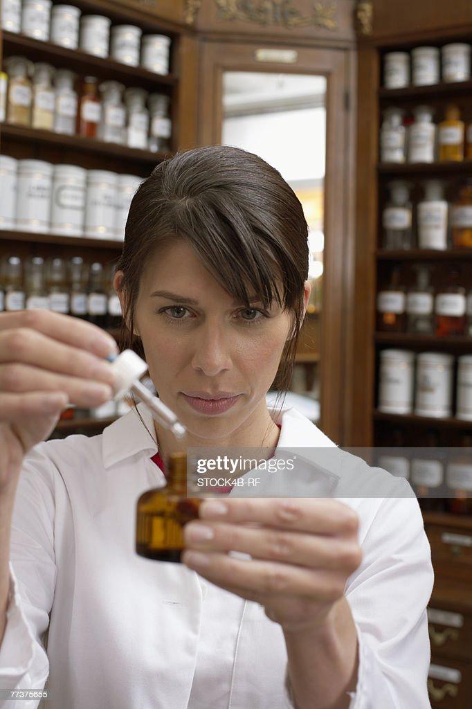 Female pharmacist preparing drug : Photo