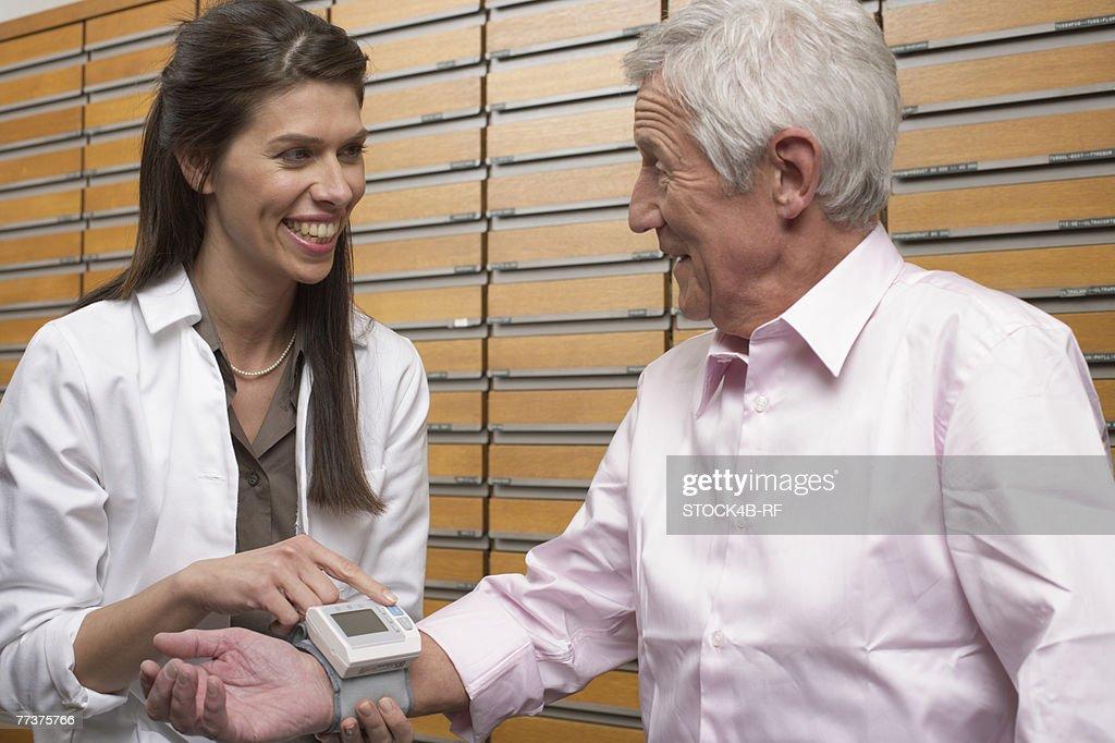 Female pharmacist taking customer's blood pressure  : Photo
