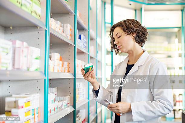 Female pharmacist taking medicine from shelf