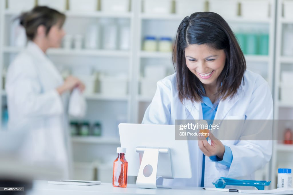Female pharmacist uses computer in pharmacy : Stock Photo