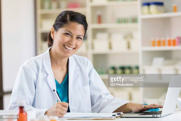 female pharmacist uses laptop to check inventory - contact list stock photos and pictures
