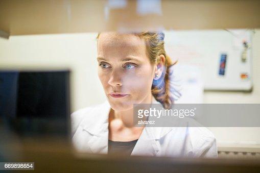 Female pharmacist using computer in store