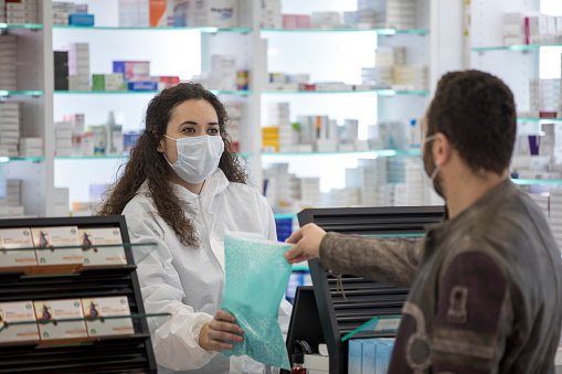 Female pharmacist wearing a surgical mask gives medication to the patient 1219410415
