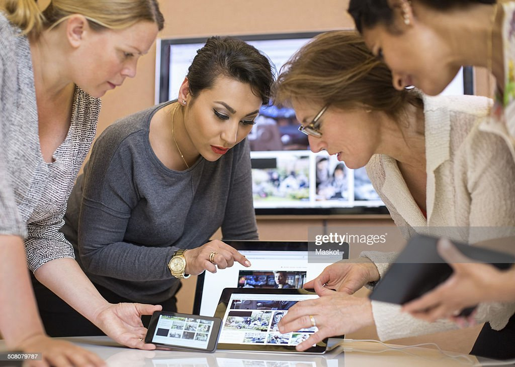 Female photo editors discussing over digital tablet in creative office : Stock Photo