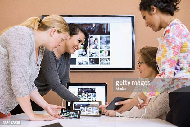Female photo editors using various technologies in creative office