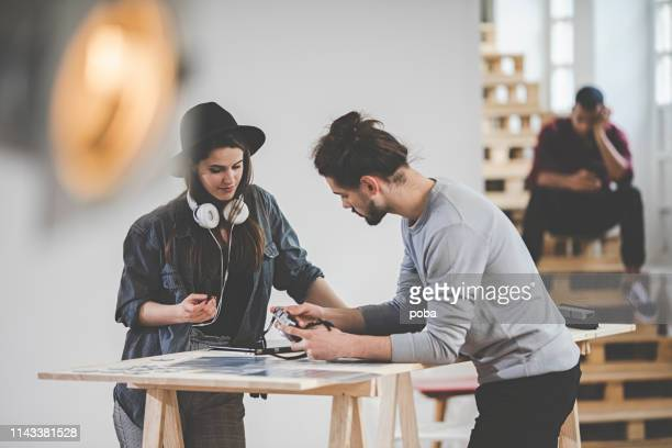 female photographer and assistant preparing photo shoot in studio - behind the scenes stock pictures, royalty-free photos & images