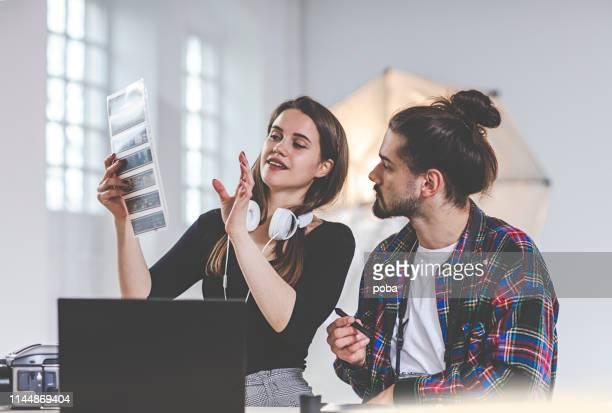 fotografin und assistentin bei der vorbereitung des fotoshootings im studio - dia stock-fotos und bilder