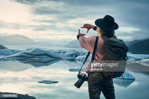 female photographer at glacier lagoon. sunset - photographer stock photos and pictures