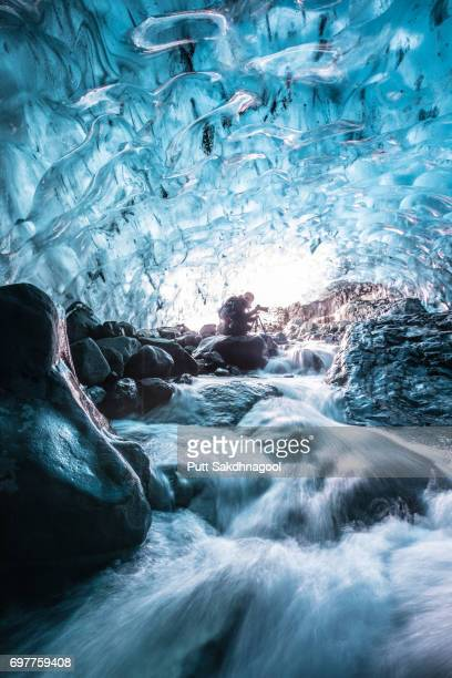 A Female Photographer in Glacial Ice Cave with Waterfall