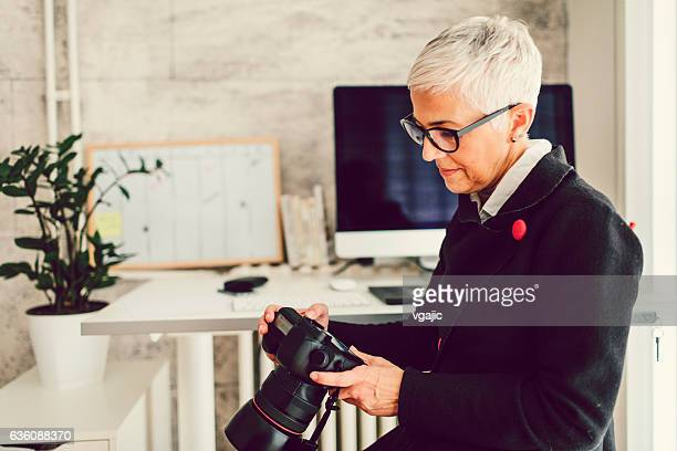 Female Photographer In Her Home Office.