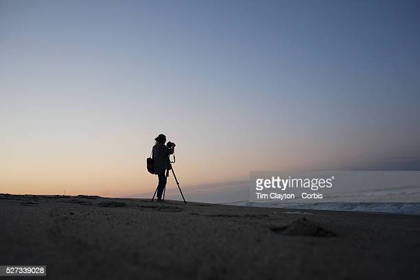 A female photographer photographs sunrise on Cisco Beach Nantucket Nantucket Island Massachusetts USA Photo Tim Clayton