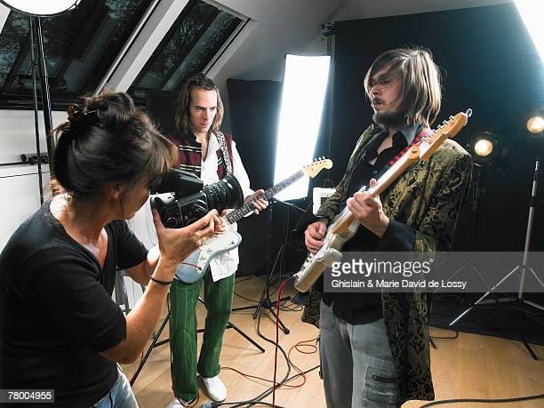 Female photographer shooting two electric guitar players in studio.