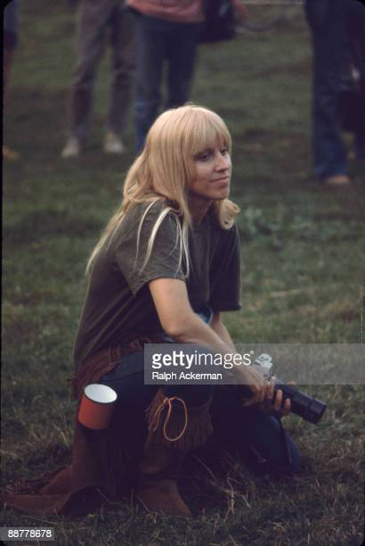 A female photographer sits with camera at the ready while attending the Woodstock Music Festival Bethel NY August 1969