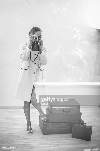 Female Photographer standing beside her Suitcases