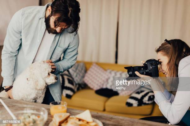 Female photographer taking a photo of a curly dog