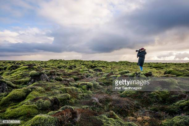 a female photographer taking a photo on lava moss field in iceland - moody sky stock pictures, royalty-free photos & images