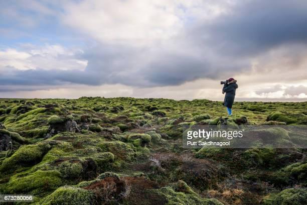 a female photographer taking a photo on lava moss field in iceland - sesion fotografica fotografías e imágenes de stock