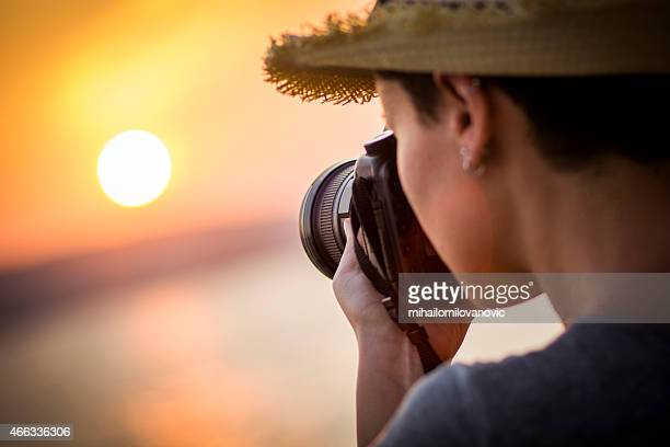 Female photographer taking a picture of the sunset