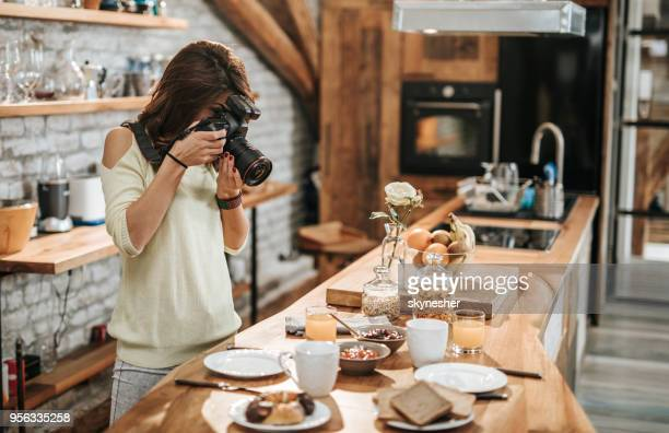 female photographer taking photos of food at dining table. - hobbies stock pictures, royalty-free photos & images